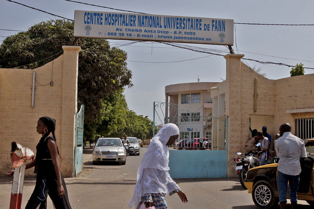 Women walk past the entrance to the  University Hospital Fann, where a man is being treated for symptoms of the Ebola virus in Dakar, Senegal,  Friday, Aug. 29, 2014. (AP Photo/Jane Hahn)