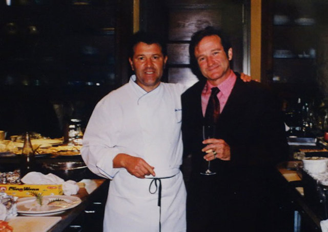 """Chef Julian Serrano and Robin Williams are shown at an Oscar party after Williams won the Oscar for Best Supporting Actor for """"Good Will Hunting"""" in 1989. (Courtesy)"""