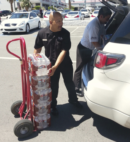 Park Place Infiniti valet Jesus Mijarez and pre-owned sales assistant Richard Sepulveda load bottled water donations to deliver to The Shade Tree shelter for women and children. The dealership spo ...