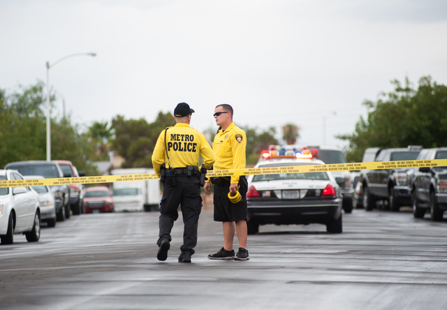 Las Vegas police officers communicate with each other while securing a northeast valley neighborhood in Las Vegas on Sunday, August 3, 2014. (Martin S. Fuentes/Las Vegas Review-Journal)