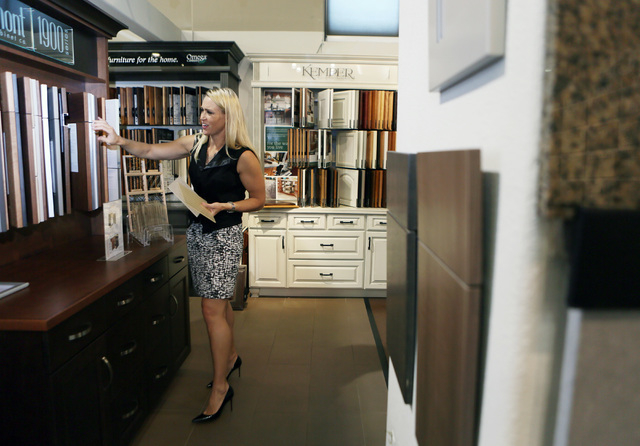 Michelle Roche looks through samples for a client while visiting the showroom at ProSource Friday, Aug. 1, 2014, in Las Vegas. Roche, who is an interior designer and owner of Parlor 430, won the 2 ...