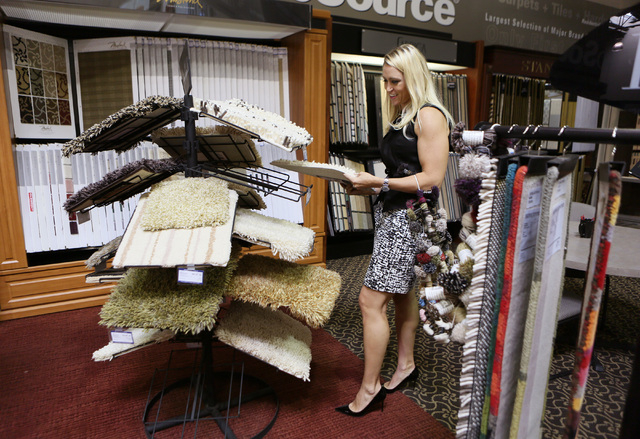 Michelle Roche looks through carpet samples for a client while visiting the showroom at ProSource Friday, Aug. 1, 2014, in Las Vegas. Roche, who is an interior designer and owner of Parlor 430, wo ...