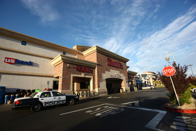 A Las Vegas police officer sits in a patrol car outside of Smith's grocery store at Charleston Boulevard and Hualapai Way, Wednesday, Aug. 20, 2014. Two people robbed the gaming area of the store  ...