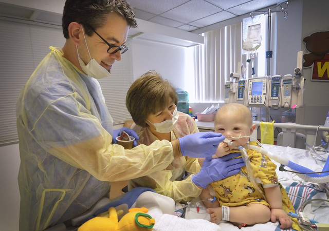 Pediatric speech pathologist Dale Whitman, left, feeds Eric Ocegueracuevas as physical therapist Carmelita Lukban steadies the baby in the pediatric intensive care unit at the Children's Hospital  ...