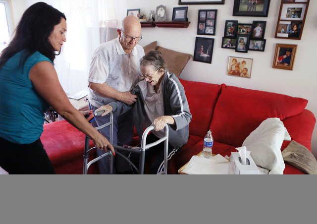 Shirley Andrews, right, gets up to use her walker with the help of her daughter-in-law Susie Avecilla, from left, and husband Richard in her home Thursday, July 24, 2014, in Las Vegas. After a lon ...