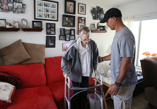 Shirley Andrews, right, prepares to sit down after using her walker with the help of her son Carlos Avecilla at her home Thursday, July 24, 2014, in Las Vegas. After a long search for treatment, t ...