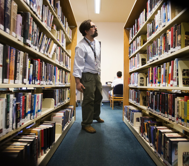 Stephen Platt, branch manager at Green Valley Library, 2797 N. Green Valley Parkway, in Henderson searches for a book for a patron on Tuesday, July 22, 2014. Librarians say the role of libraries i ...