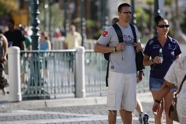 A couple waits to cross the street near The Venetian casino-hotel in Las Vegas Tuesday, Aug. 26, 2014. Clark County officials are considering a ban of glass bottles on the Strip. (Erik Verduzco/La ...