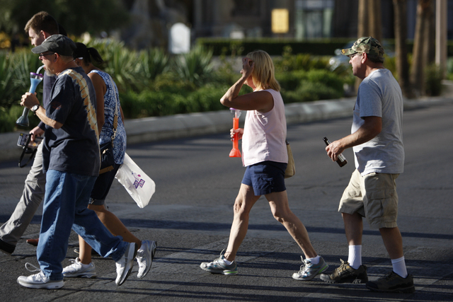 A couple holding their drinks cross the street near Caesars Palace casino-hotel in Las Vegas Tuesday, Aug. 26, 2014. Clark County officials are considering a ban of glass bottles on the Strip. (Er ...