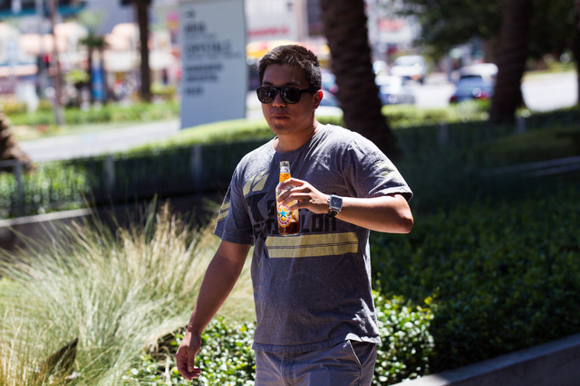 Justin Teng of Cupertino, Calif. carries a glass bottle of beer while walking on the Strip near Cosmpolitan in Las Vegas on Tuesday, Aug. 26, 2014. Clark County officials are considering a ban of  ...
