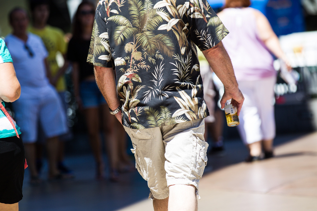 A man carries a glass bottle of beer while walking on the Strip near CityCenter in Las Vegas on Tuesday, Aug. 26, 2014. Clark County officials are considering a ban of glass bottles on the Strip.  ...