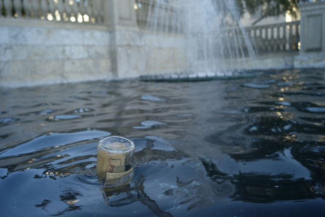 A glass bottle floats in a fountain area outside of Caesars Palace in Las Vegas on Wednesday morning, Aug. 27, 2014. Clark County officials are considering a ban of glass bottles on the Strip. (Ch ...