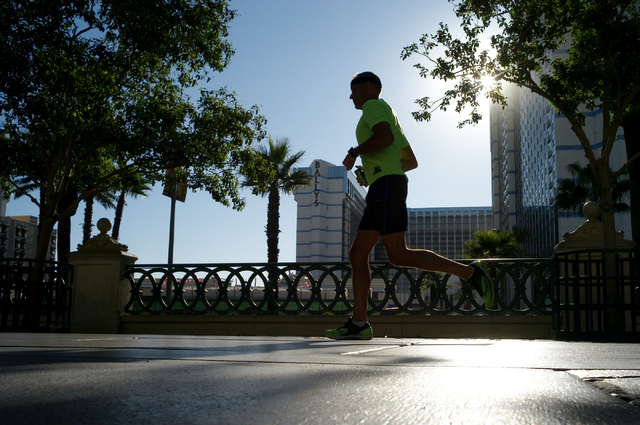 A man runs along the Strip near the Bellagio in Las Vegas on Wednesday morning, Aug. 27, 2014. (Chase Stevens/Las Vegas Review-Journal)
