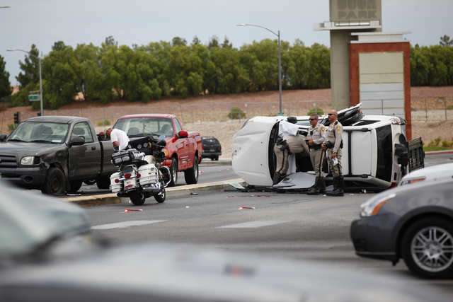 A rollover SUV crash is seen at Alta Drive and Rampart Boulevard in Las Vegas on Monday, Aug. 18, 2014. The SUV flipped over while making a right turn onto Alta Drive, and collided with a truck in ...