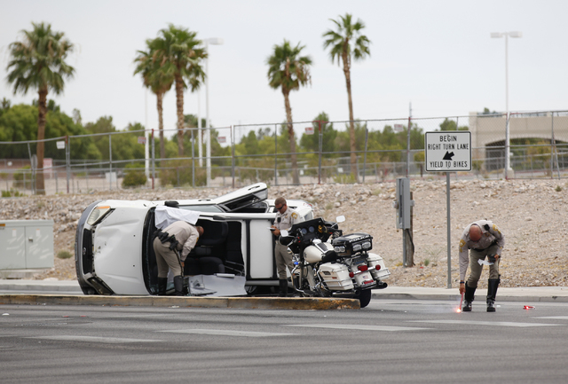 A police officer re-lights a flare where a rollover SUV crash occurred at Alta Drive and Rampart Boulevard in Las Vegas on Monday, Aug. 18, 2014. The SUV flipped over while making a right turn ont ...
