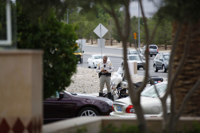 A police officer is seen where a rollover SUV crash occurred at Alta Drive and Rampart Boulevard in Las Vegas on Monday, Aug. 18, 2014. The SUV flipped over while making a right turn onto Alta Dri ...