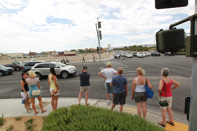 People look over at where a rollover SUV crash occurred while waiting to cross the street at Alta Drive and Rampart Boulevard in Las Vegas on Monday, Aug. 18, 2014. The SUV flipped over while maki ...
