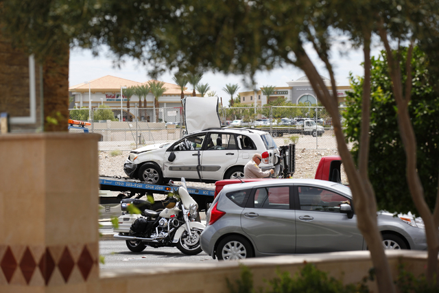 An SUV which rolled over during a right turn and hit another vehicle at Alta Drive and Rampart Boulevard is seen being loaded onto a tow truck in Las Vegas on Monday, Aug. 18, 2014. Two people in  ...