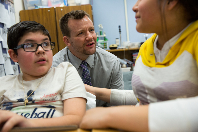 Students Alex Bustos, (cq) left, and Calixta Rincon, right, (cq) talk with their fifth-grade teacher, Justin Brecht, center, Friday, Feb. 21, 2014 at John F. Mendoza Elementary School. Brecht is r ...