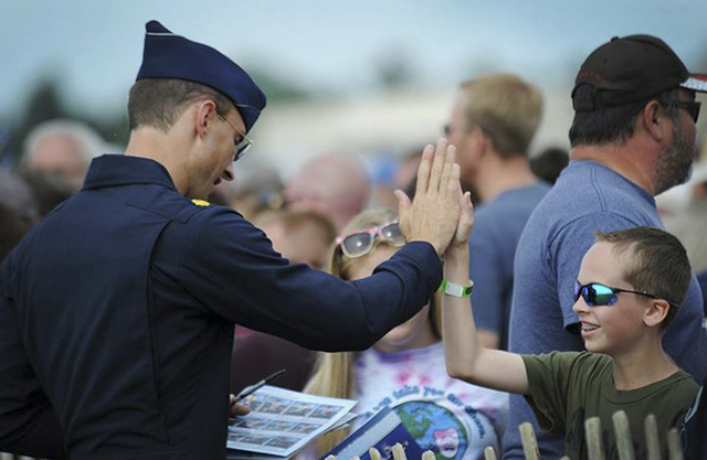 Maj. Tyler Ellison, Thunderbird 7, operations officer, interacts with a young fan following the performance at the Battle Creek Field of Flight Air Show & Balloon Festival, in Battle Creek, Mich., ...