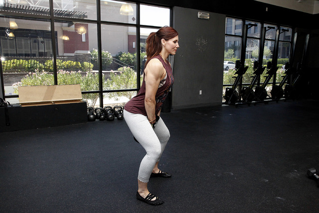 Trainer Laura Salcedo demonstrates the starting position for the kettle bell swing at CrossFit Mountain's edge in Las Vegas on Tuesday, June 24, 2014. (Justin Yurkanin/Las Vegas Review-Journal).