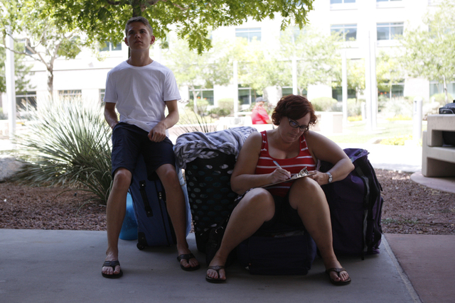 Jake Petmecky, left, 15, with his mother Erin Maloney, wait for his sister Janine outside of the Dayton Complex residence halls during freshmen move in day at UNLV in Las Vegas Wednesday, Aug. 20, ...