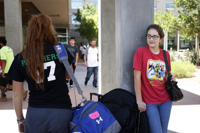 Dana Scinta, left, 18, makes a call to find her dormitory as her sister Madison, 15, looks on outside of the Dayton Complex residence halls during freshmen move in day at UNLV in Las Vegas Wednesd ...