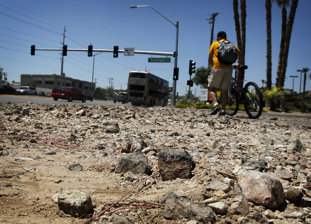 A cyclist walks his bike past a large deposit of debris at the intersection of Sahara and Richfield the day after flash floods swept through Las Vegas on Tuesday, Aug. 5, 2014. (Jason Bean/Las Veg ...