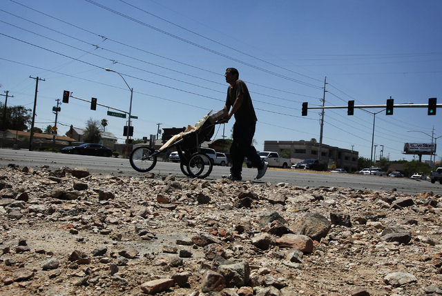 A pedestrian makes his way past a large deposit of debris at the intersection of Sahara and Richfield the day after flash floods swept through Las Vegas on Tuesday, Aug. 5, 2014. (Jason Bean/Las V ...