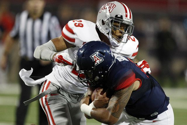 UNLV defensive back Tajh Hasson (29) tackles Arizona quarterback Anu Solomon (12) during the first half of an NCAA college football game, Friday, Aug. 29, 2014, in Tucson, Ariz. (AP Photo/Rick Scu ...