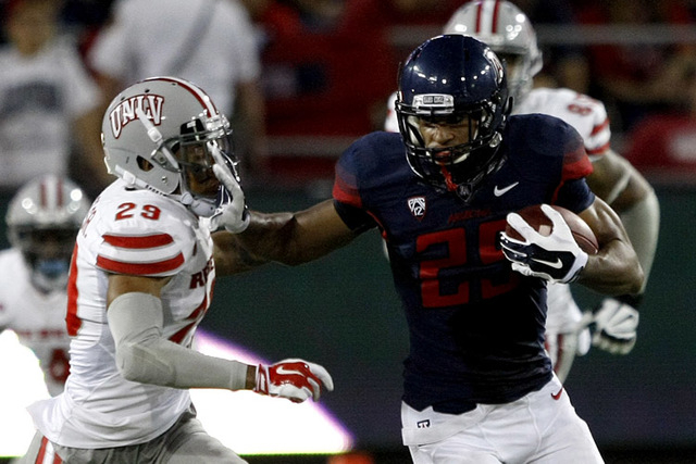 Arizona running back Spencer Marciniak (25) runs away from UNLV defensive back Tajh Hasson (29) during the second half of an NCAA college football game, Friday, Aug. 29, 2014, in Tucson, Ariz. (AP ...
