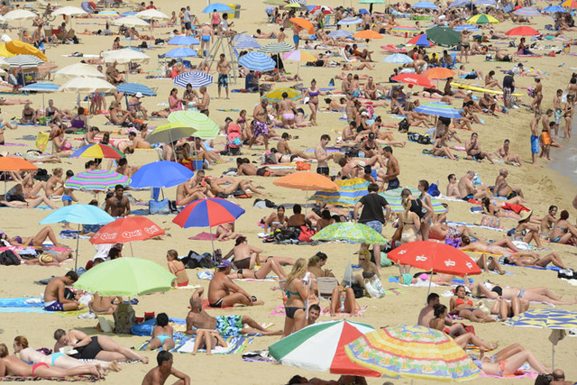 People enjoy the sun at Barceloneta Beach in Barcelona, in this file photo. La Barceloneta residents have taken to the streets several days in a row to protest against a rise in unruly tourism and ...
