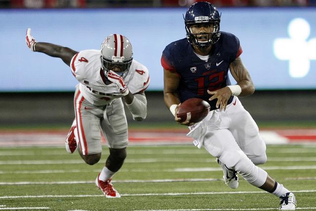 Arizona quarterback Anu Solomon runs away from UNLV defensive back Sidney Hodge during the second half of an NCAA college football game, Friday, Aug. 29, 2014, in Tucson, Ariz. (AP Photo/Rick Scuteri)