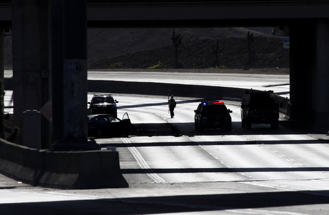 A Nevada Highway Parol officer examines the scene of a car wreck on the US 95 northbound side bar downtown Las Vegas on Sunday, August 31, 2014. The northbound section of the road was closed while ...