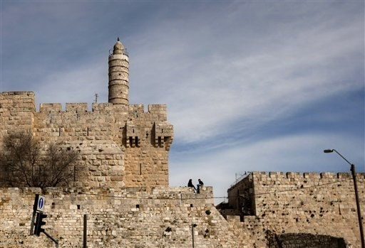 A couple sits next to the Tower of David on the wall surrounding Jerusalem's Old City. 2014 was supposed to be a record-breaking year for tourist visits to Israel. But all that changed when this s ...