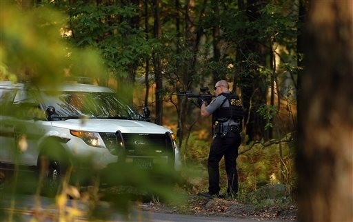 A Pennsylvania State Trooper draw's his weapon in a wooded area on Snow Hill Road in Price Township, Pa., during a massive manhunt for suspected killer Eric Frein on Sunday, Sept. 21, 2014, near C ...