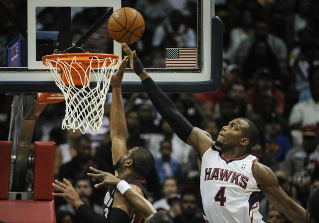 Atlanta Hawks forward Paul Millsap (4) gets his hand on a shot by Miami Heat guard Dwyane Wade (3) during the first half of an NBA basketball game on Saturday, April 12, 2014, in Atlanta. (AP Phot ...