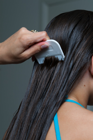 Mom combing nits out of young girls hair