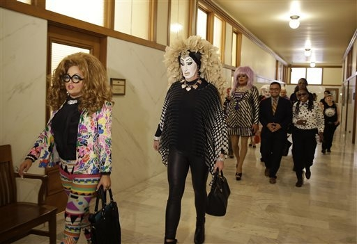 Drag queens from left, Lil Ms. Hot Mess, Sister Roma and Heklina walk to a news conference after meeting with city supervisor David Campos, fourth from left, in his office at City Hall, Wednesday, ...