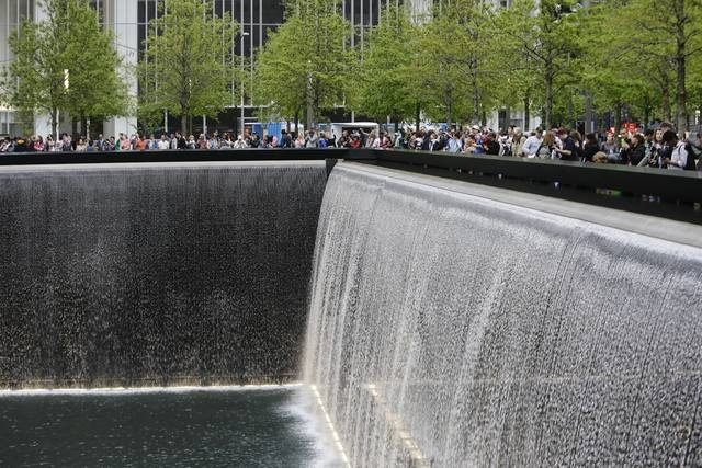 "This file photo shows patrons visiting the pools at The 9/11 Memorial near the World Trade Center in New York.  President Barack Obama praised the new Sept. 11 museum as ""a sacred place of healing ..."