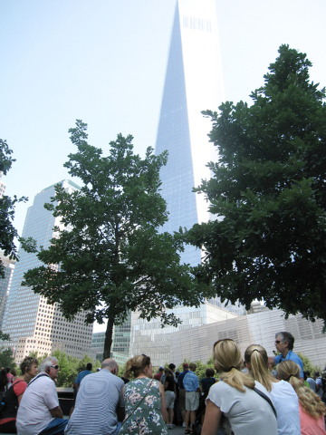 This photo shows Brenda Berkman, in blue, leading a tour of the 9/11 Memorial in Lower Manhattan. The tour is sponsored by the 9/11 Tribute Center. The guides include individuals who survived the  ...