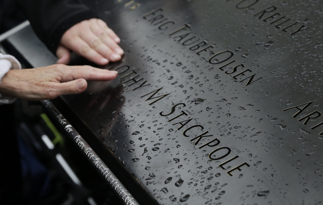 This file photo shows people touching the engraved name of a victim of the Sept. 11, 2001 attacks at the National September 11 Memorial & Museum in New York. The memorial has been visited by nearl ...