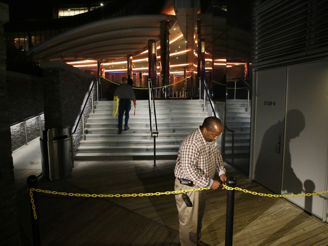 A casino worker secures a plastic chain across The Boardwalk entrance to the Revel Hotel Casino early Tuesday, Sept. 2, 2014, in Atlantic City, N.J.  The casino section of the Revel closed at 6:30 ...