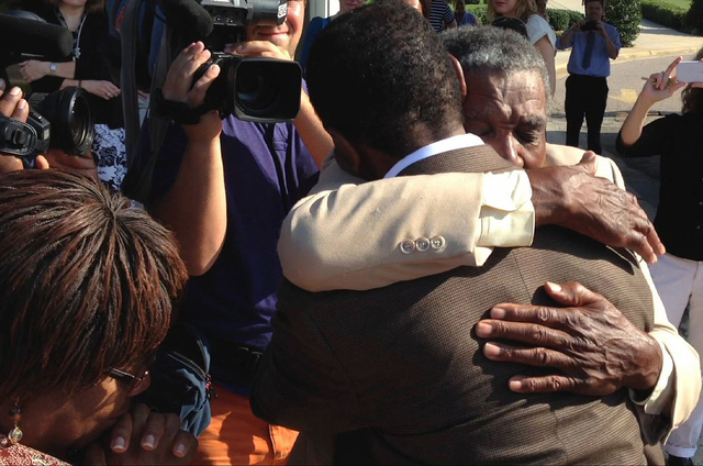 James McCollum, facing camera, embraces his son Henry following the younger man's release from Central Prison in Raleigh, N.C., on Wednesday, Sept. 3, 2014. Henry McCollum spent more than 30 years ...