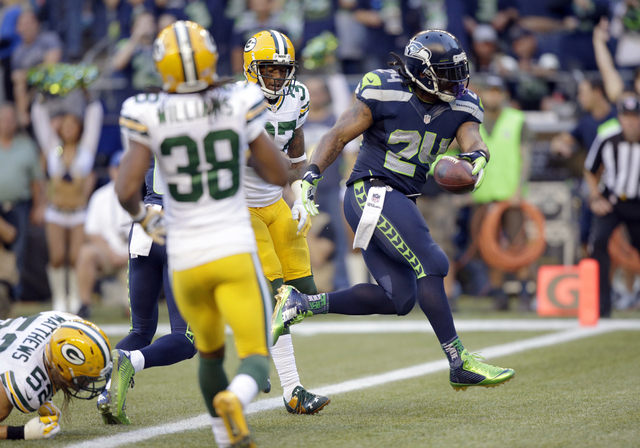 Seattle Seahawks running back Marshawn Lynch (24) scores a touchdown in the first half of an NFL football game against the Green Bay Packers, Thursday, Sept. 4, 2014, in Seattle. (AP Photo/Stephen ...