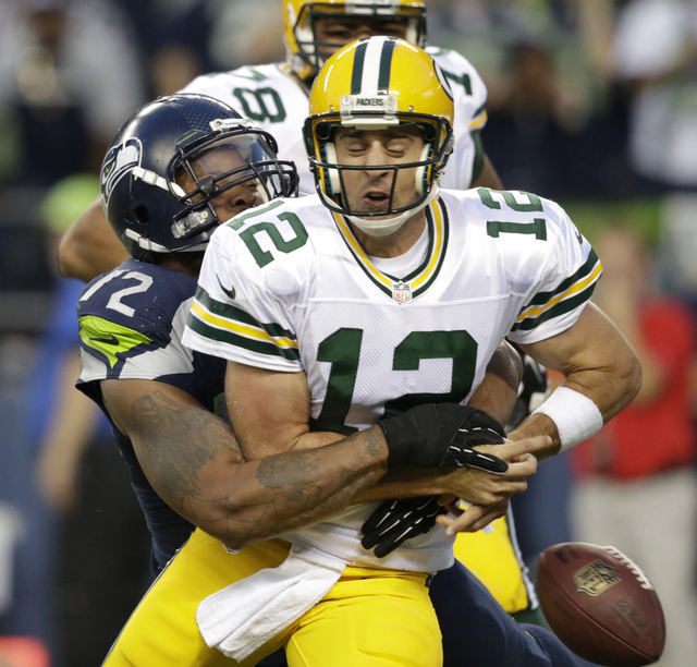 Seattle Seahawks defensive end Michael Bennett forces Green Bay Packers quarterback Aaron Rodgers to fumble in the second half of an NFL football game, Thursday, Sept. 4, 2014, in Seattle. A Packe ...