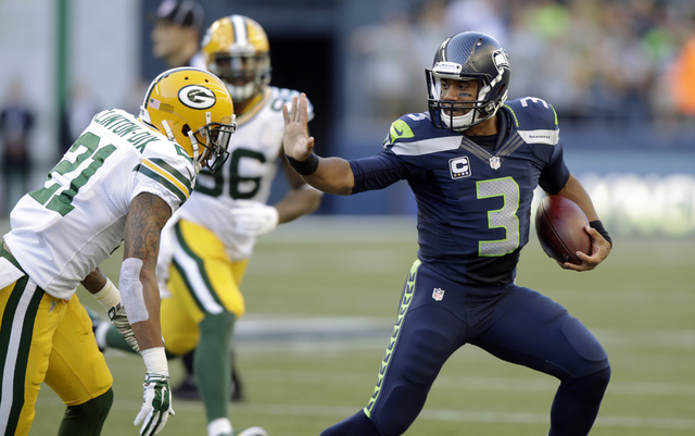 Seattle Seahawks quarterback Russell Wilson (3) avoids Green Bay Packers' Ha Ha Clinton-Dix (21) during the first half of an NFL football game, Thursday, Sept. 4, 2014, in Seattle. (AP Photo/Steph ...