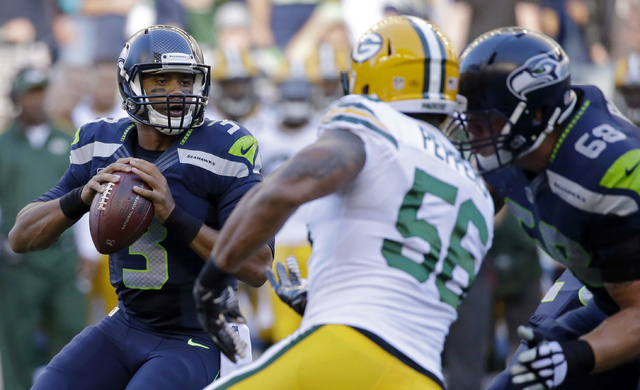 Seattle Seahawks quarterback Russell Wilson drops back to pass against the Green Bay Packers in the first half of an NFL football game, Thursday, Sept. 4, 2014, in Seattle. (AP Photo/Elaine Thompson)