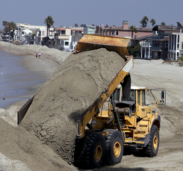 A dump truck works to pile sand on a temporary berm to protect beach front homes on, Friday, Sept. 5, 2014, in Long Beach, Calif. Southern California is in for another round of high surf generated ...