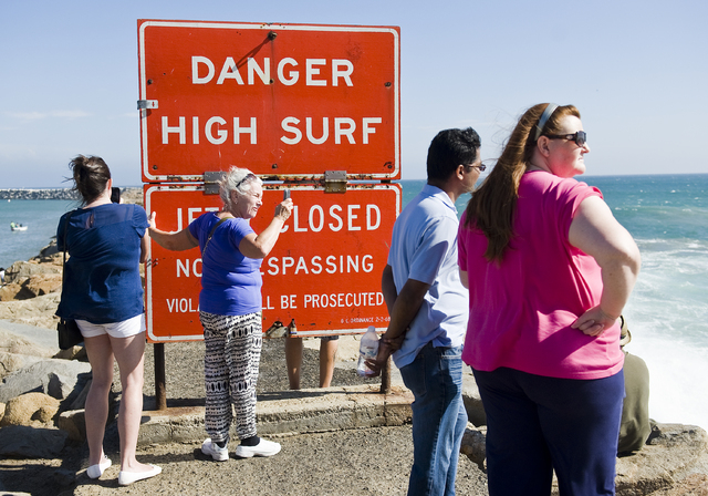 A sign warns visitors of high surf as they stand on the jetty protecting Dana Point Harbor on Saturday afternoon Sept. 6, 2014 in Dana Point, California. Hurricane Norbert in Baja California is re ...
